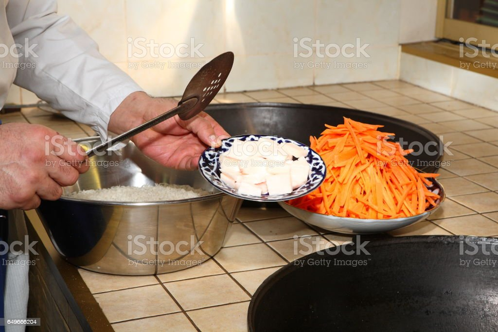 Preparation of pilaf with meat in a large bowl stock photo