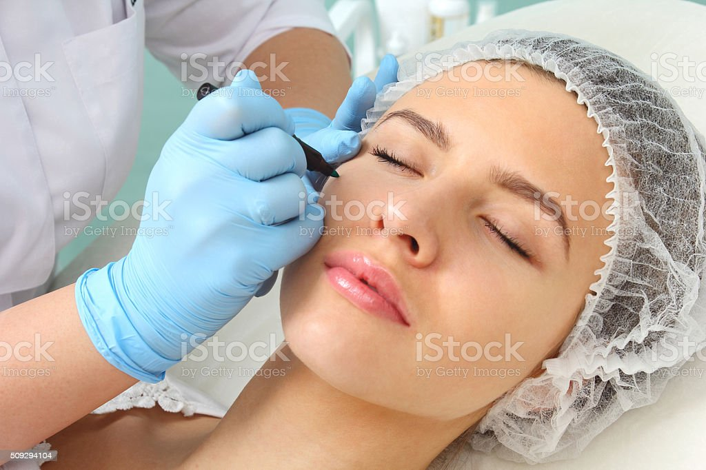 Preparation of the patient's face to a cosmetic procedure. stock photo