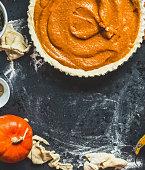 Preparation of Traditional pumpkin pie on dark rustic background