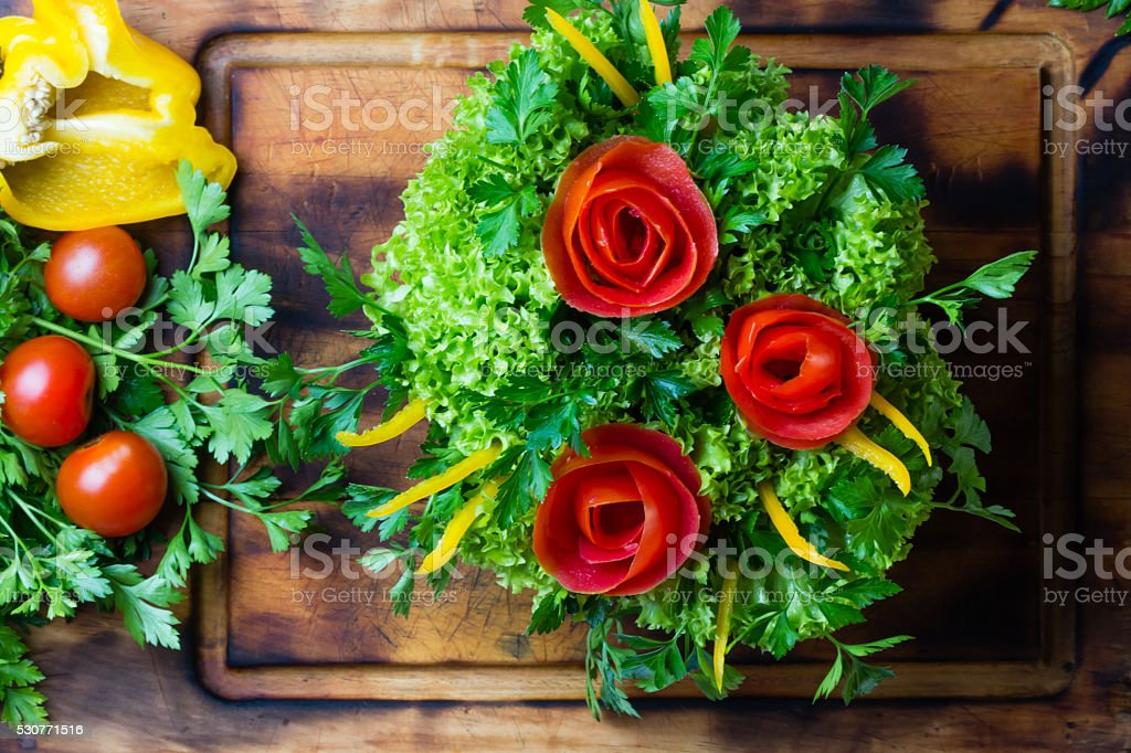 Preparation vegetable bouquet of tomatoes, lettuce, bell paper. Cutting board stock photo