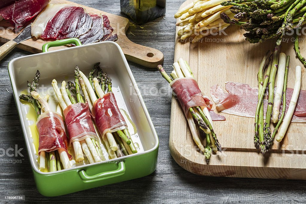 Preparations for the asparagus wrapped in Parma ham casserole royalty-free stock photo