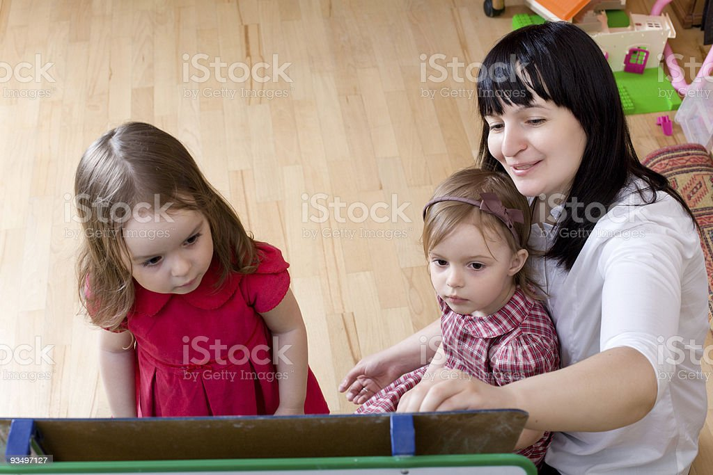Prepare to school series. Mother teaching her daughters stock photo