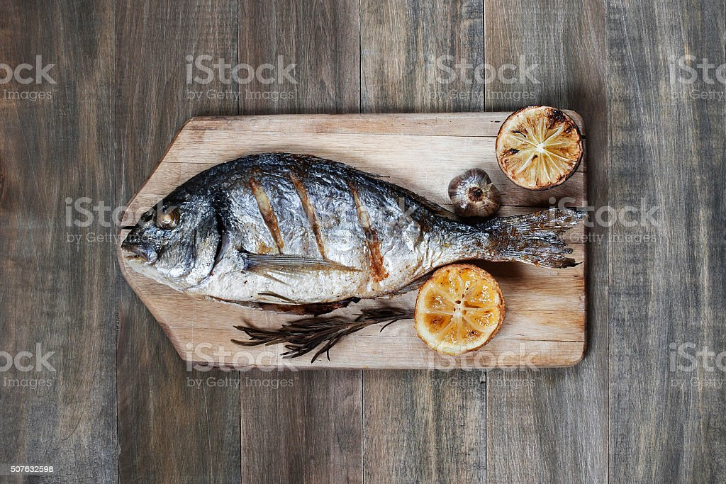 Prepared fish on on the old wooden table stock photo