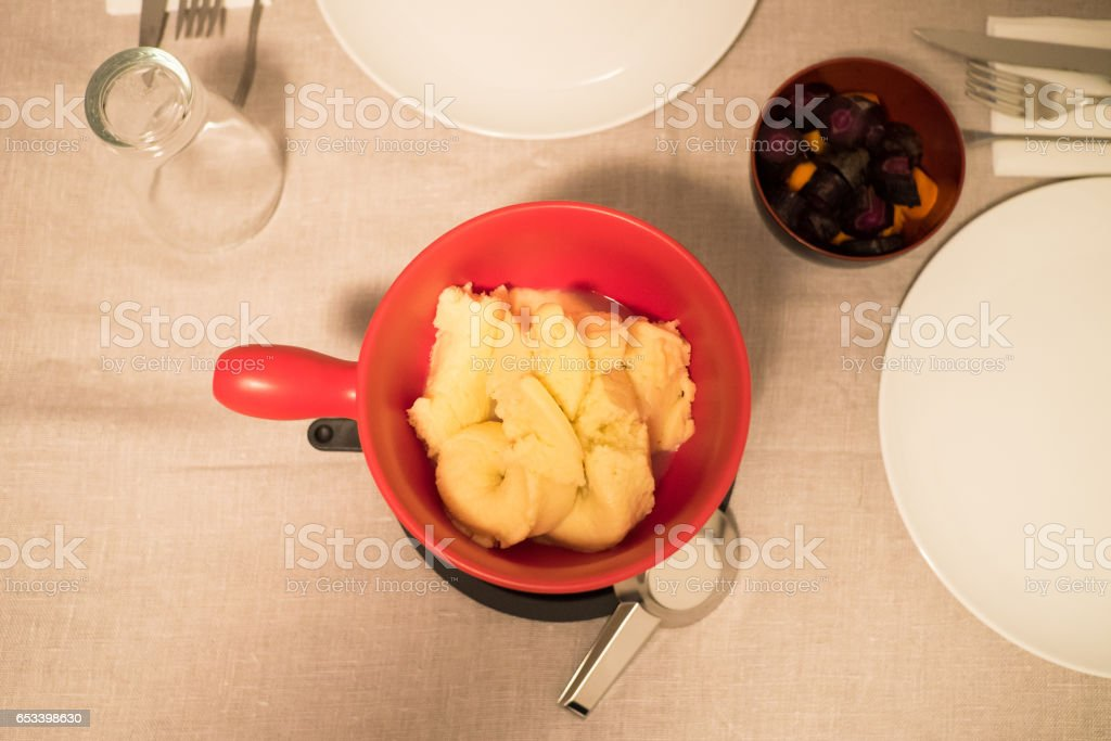 Preparing a fondue. Top view of a red pot full of cheese stock photo