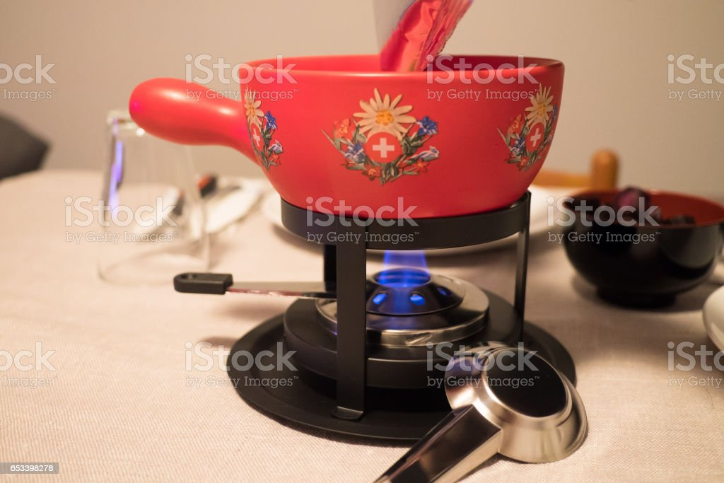 Preparing a fondue using a red Swiss caquelon pot stock photo