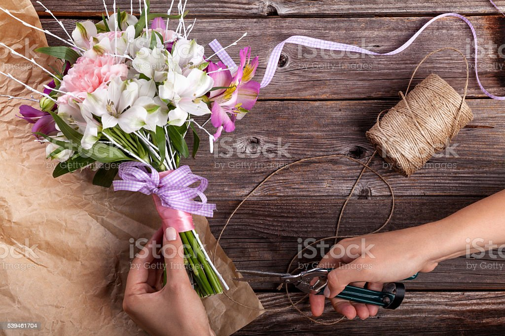 Preparing a rustic bouquet from gillyflowers and alstroemeria on stock photo