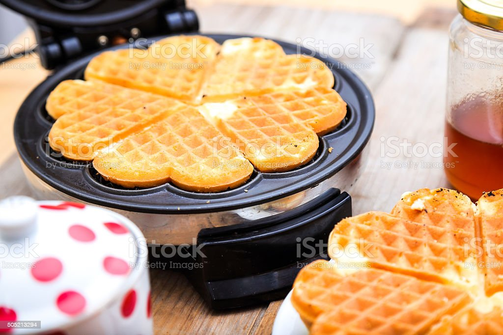 Preparing and prepared heart shaped waffles stock photo
