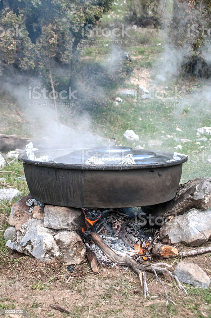 Preparing food in big pot on campfire royalty-free stock photo