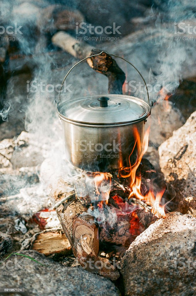Preparing food on campfire in wild camping royalty-free stock photo
