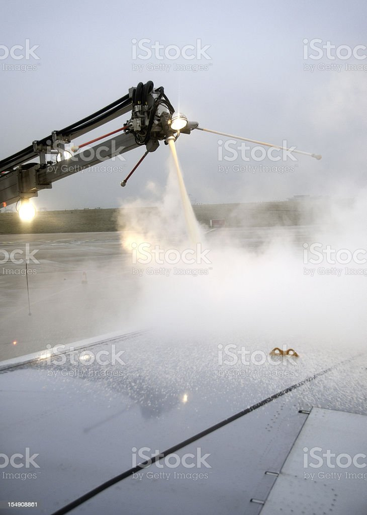 Preparing for takeoff: Airplane getting de-iced in Winter stock photo