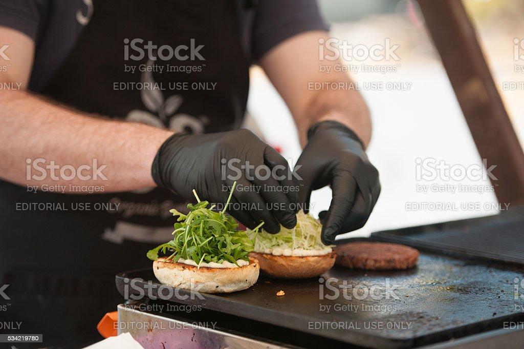 Preparing hamburger with arugula outdoors stock photo