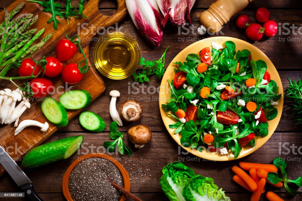 Preparing healthy salad with chia seeds on rustic wood table stock photo