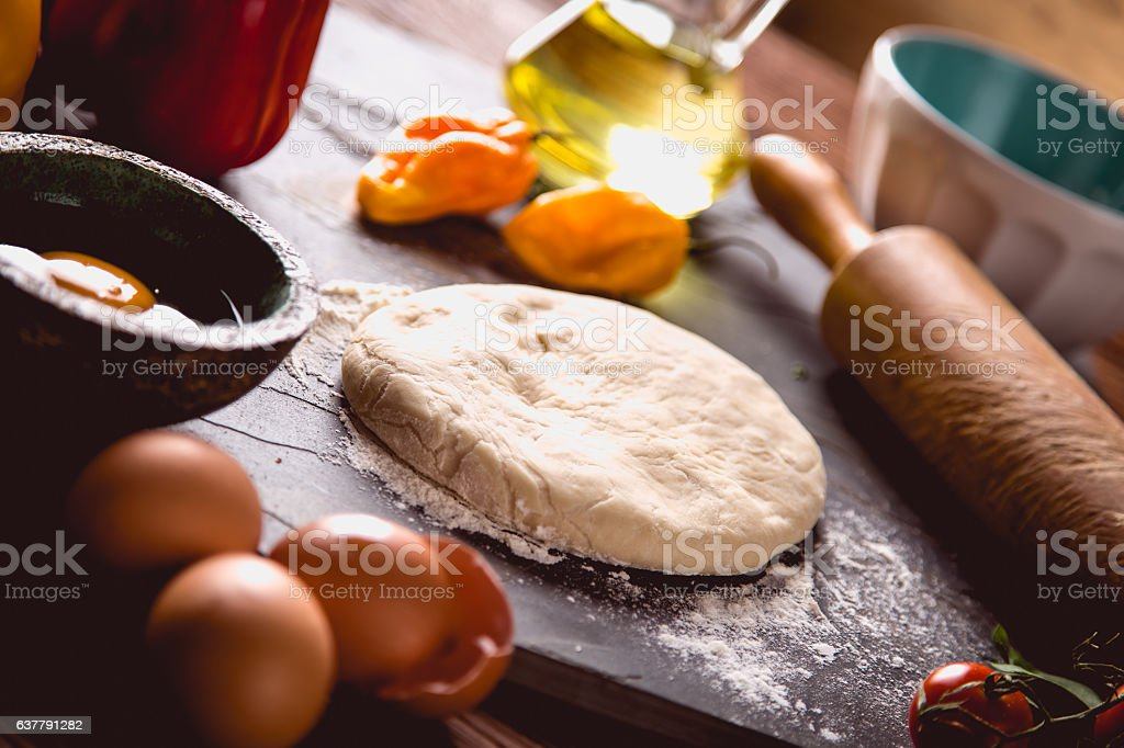 Preparing home pizza on wooden table with ingredients stock photo