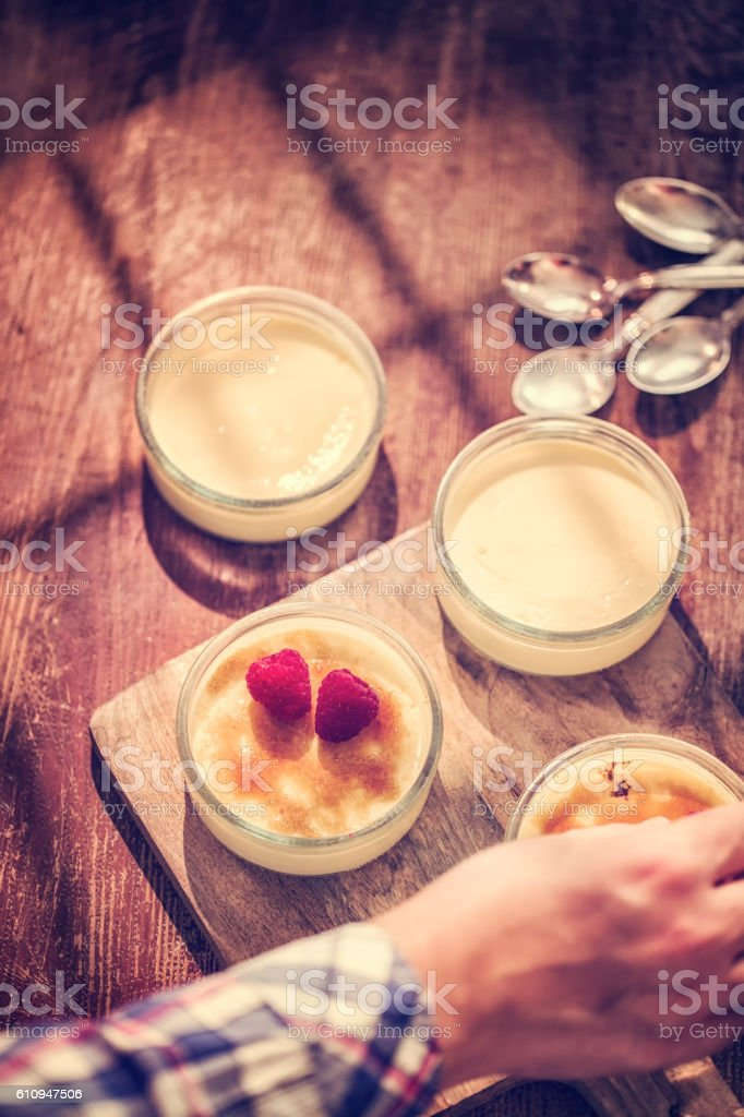 Preparing Homemade Creme Brulee with Berries stock photo