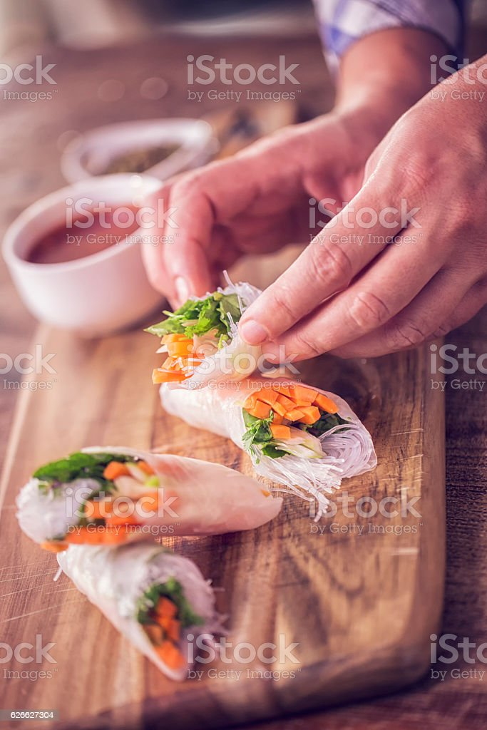 Preparing Homemade Spring Rolls with Fresh Vegetables stock photo