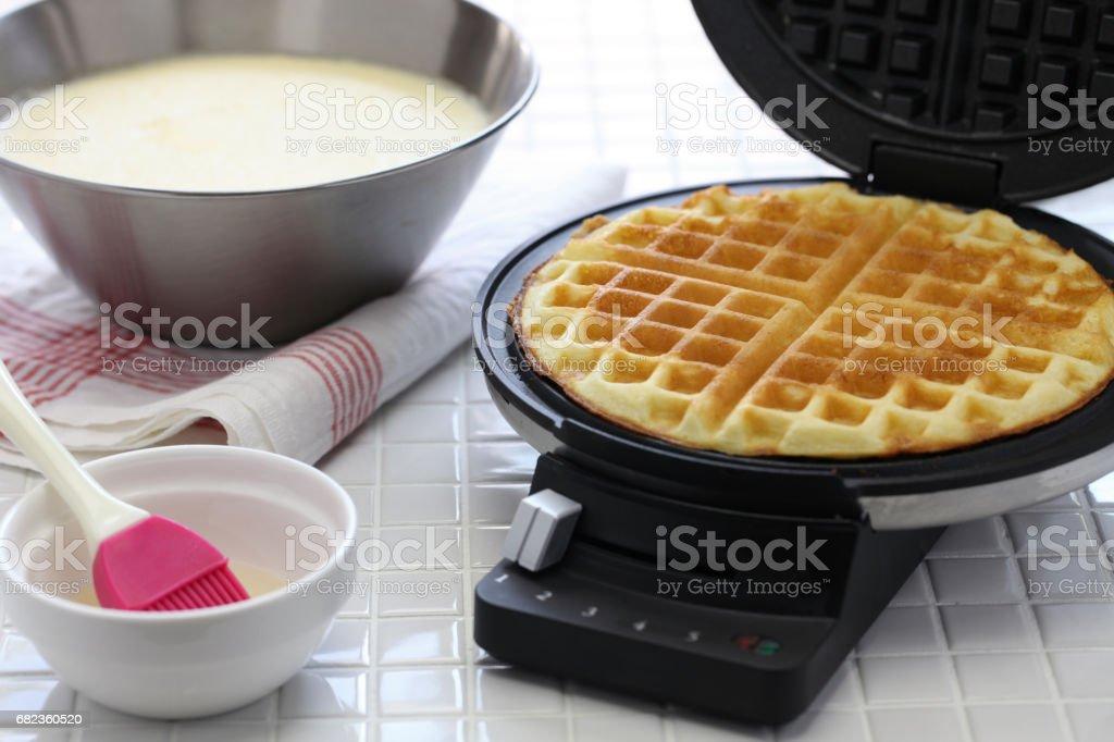 preparing homemade waffles by waffle maker machine. stock photo