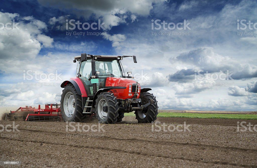 Preparing land for sowing at spring, farmer in tractor stock photo