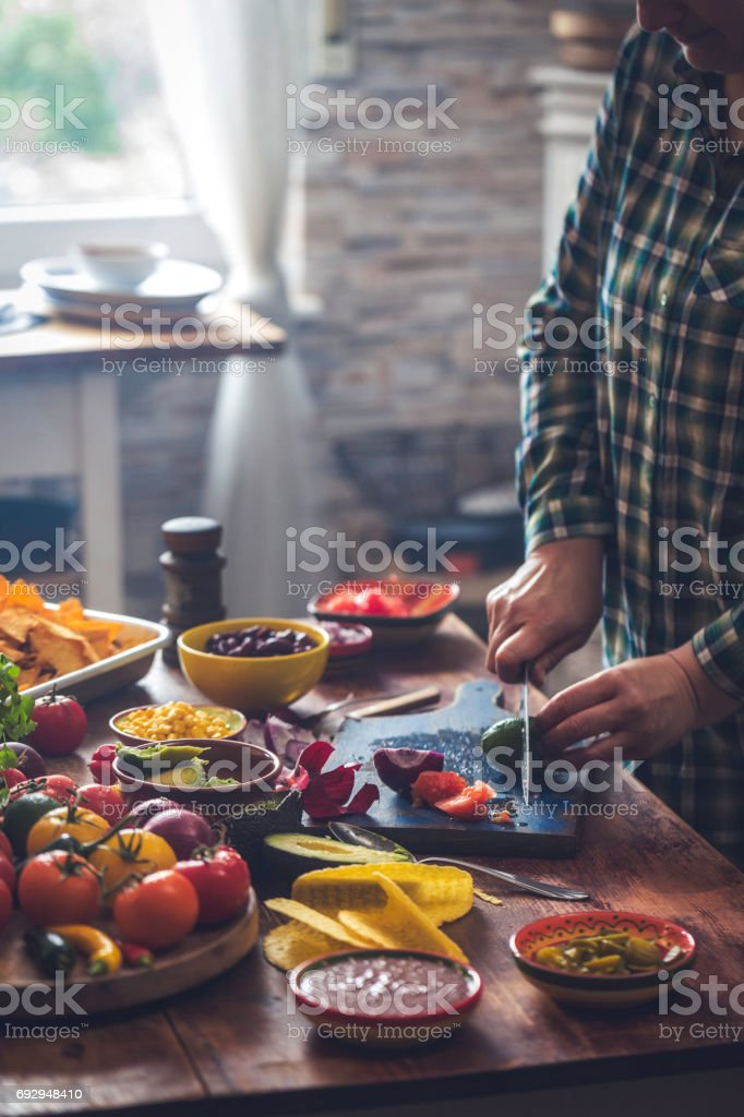 Preparing Mexican Tacos with Spicy Salsa and Guacamole stock photo