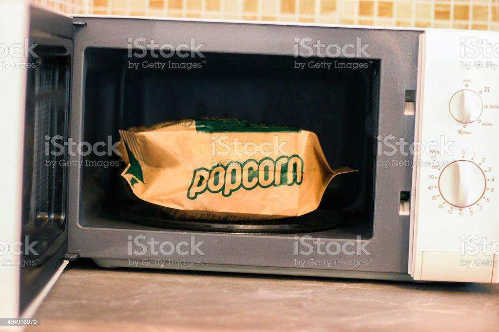 Preparing microwave popcorn stock photo