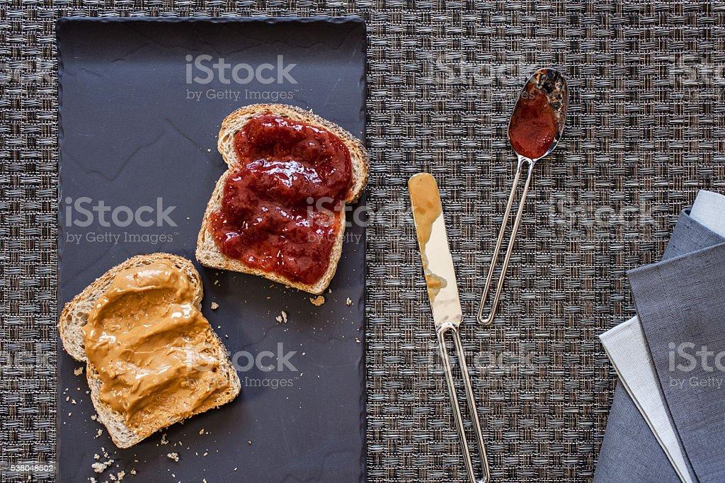 Preparing peanut butter and strawberry jam sandwich stock photo