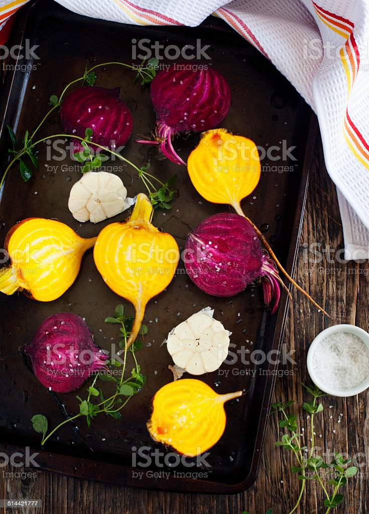 Preparing raw beetroots and garlic for roasting stock photo