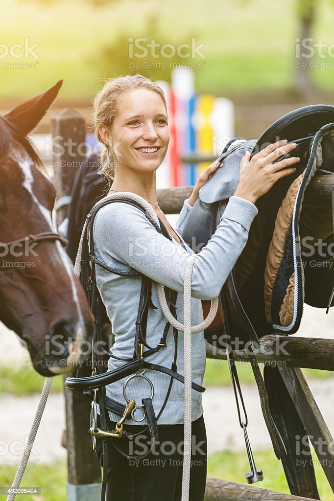 Preparing saddle for her horse happy woman horseback riding stock photo