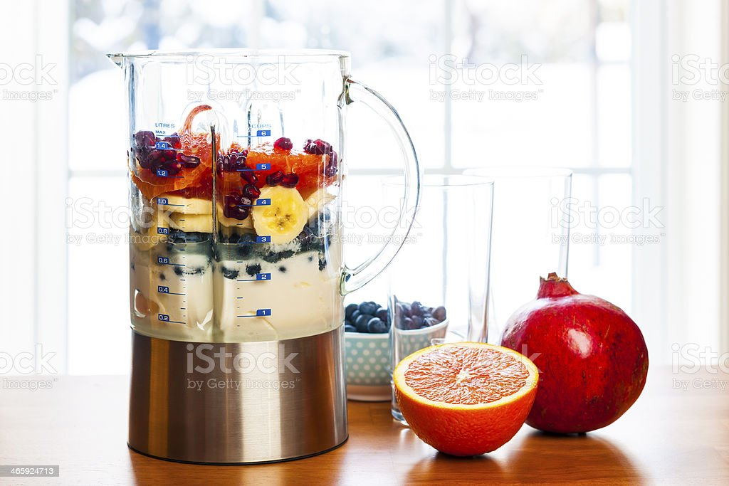 Preparing smoothies with fruit and yogurt stock photo