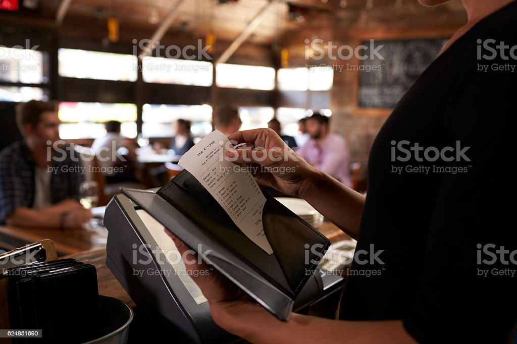 Preparing the bill at a restaurant to be taken to a table stock photo