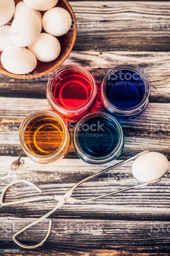 Preparing to dye eggs for Easter. Picking-up egg for dyeing. stock photo