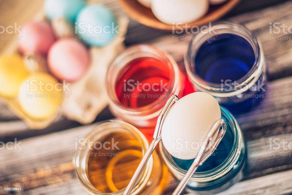 Preparing to dye eggs for Easter. Placing egg in dye. stock photo