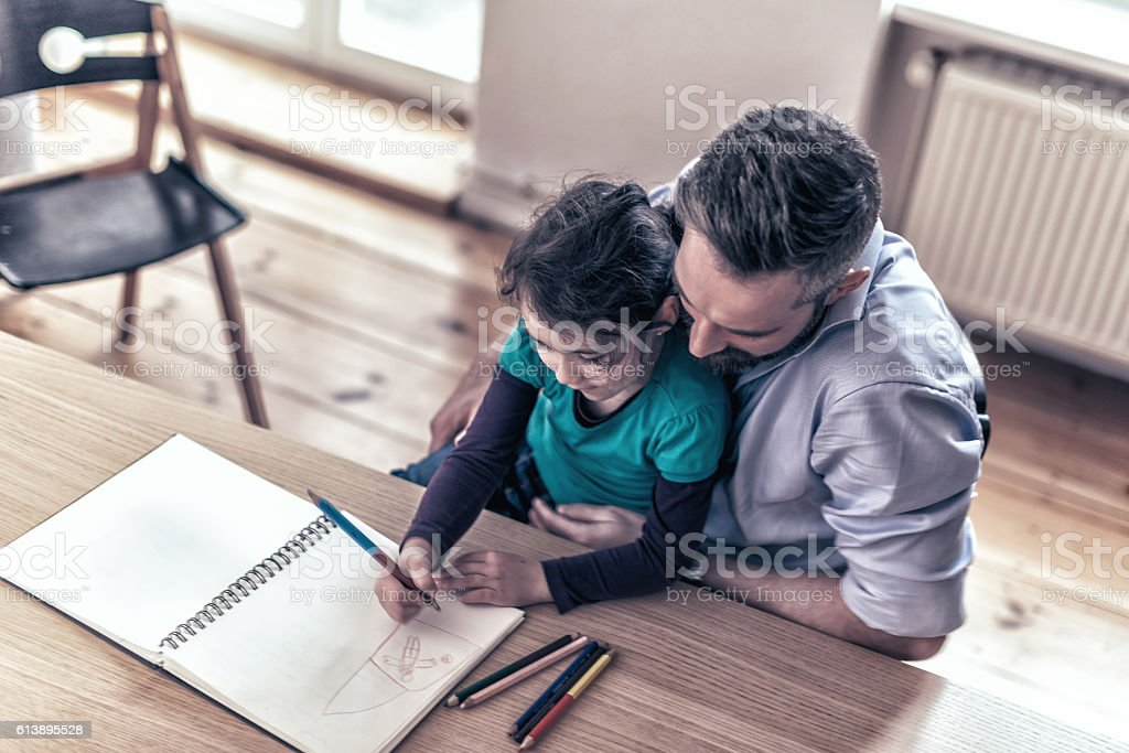 prescholar girl and  father drawing together at desk stock photo