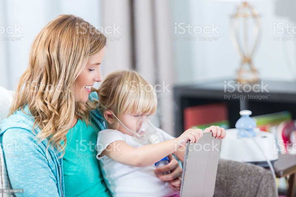 Preschool age daughter plays with tablet while receiving breathing treatment stock photo