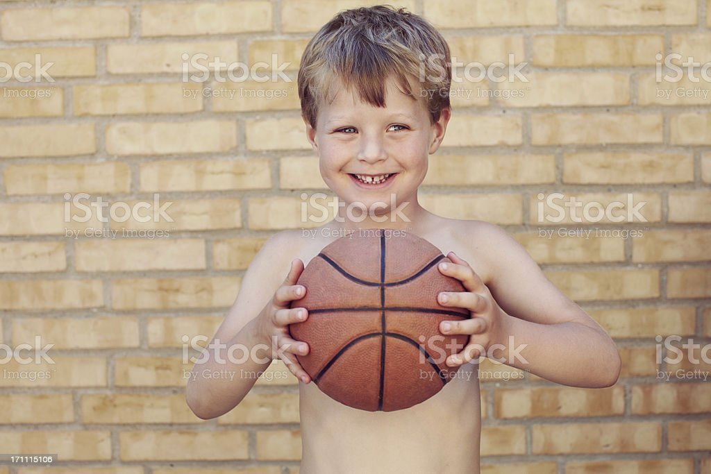 preschool boy standing in front of a brick wall stock photo