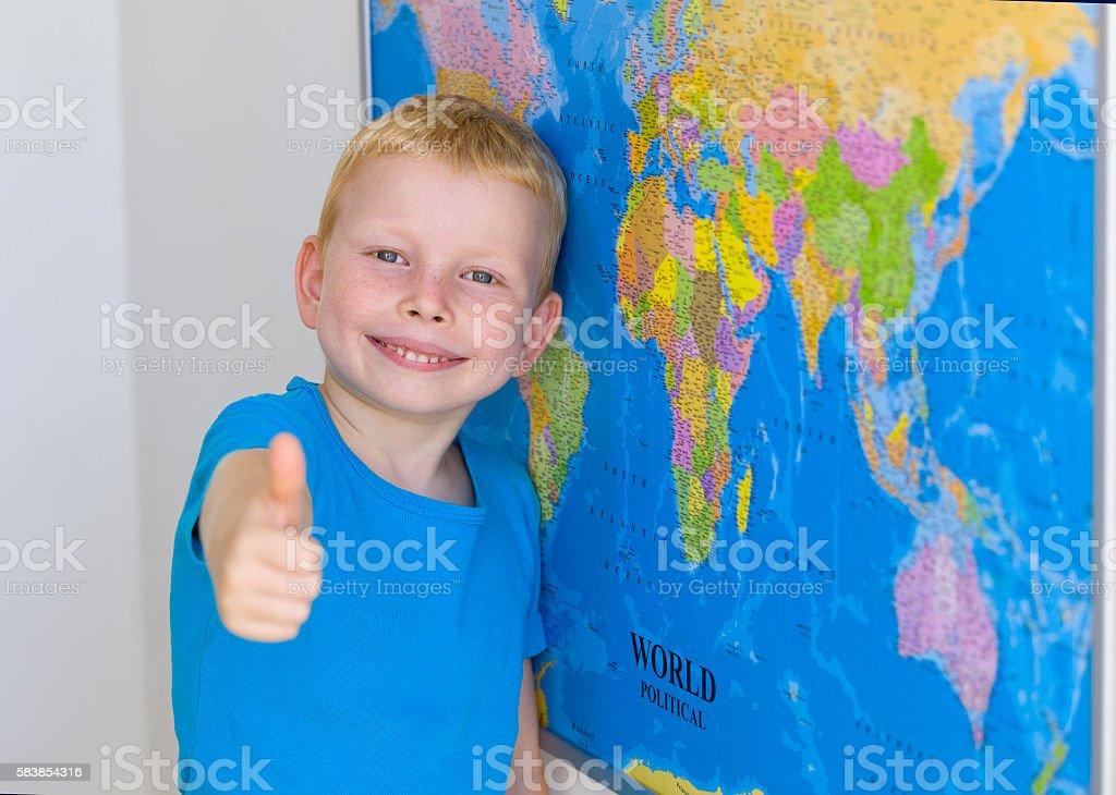 Preschool boy with world map, thumbs up stock photo
