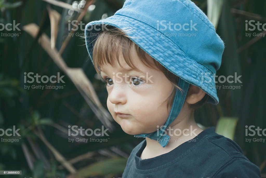 Pre-school Child in a Sunhat against a New Zealand Flax Background stock photo