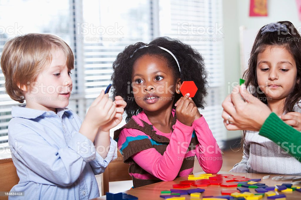 Preschool children in classroom using colorful shapes stock photo