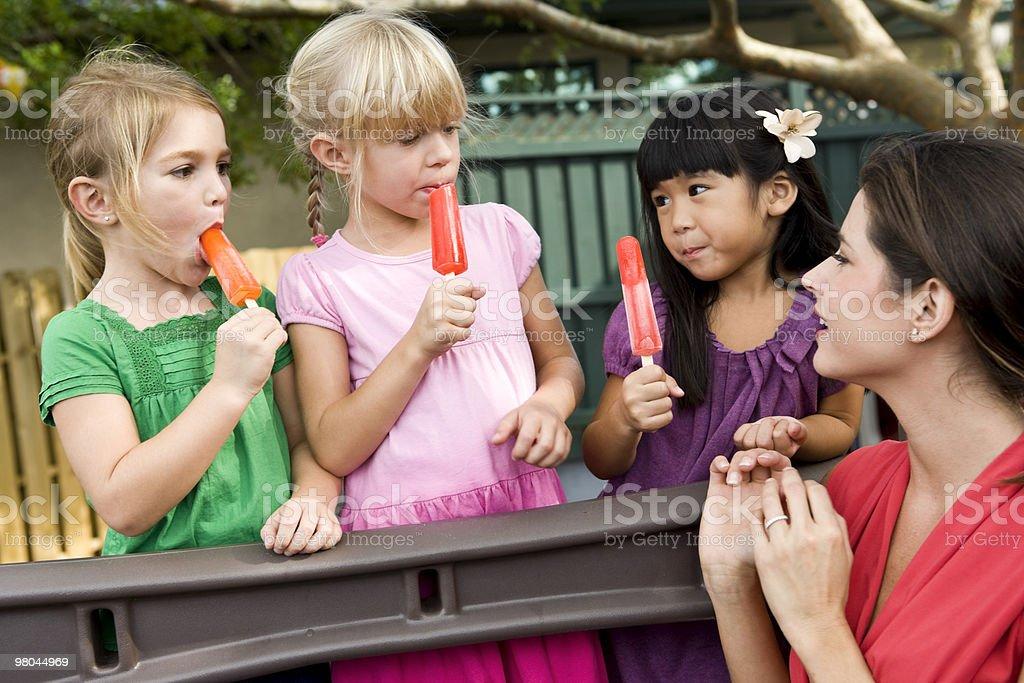 Escuela preescolar niños en patio de juegos con profesor comer paletas heladas foto de stock libre de derechos