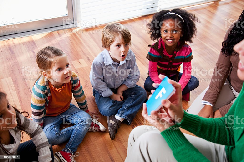 Preschool children with teachers looking at flashcards royalty-free stock photo