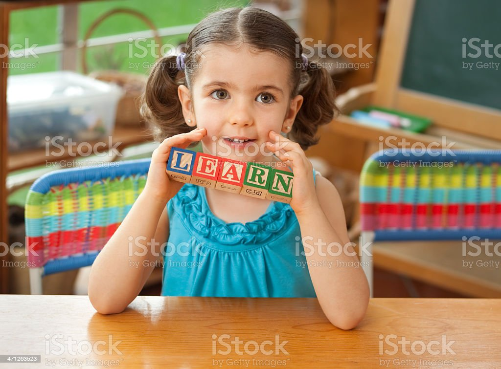 Preschool girl holding word 'learn' royalty-free stock photo
