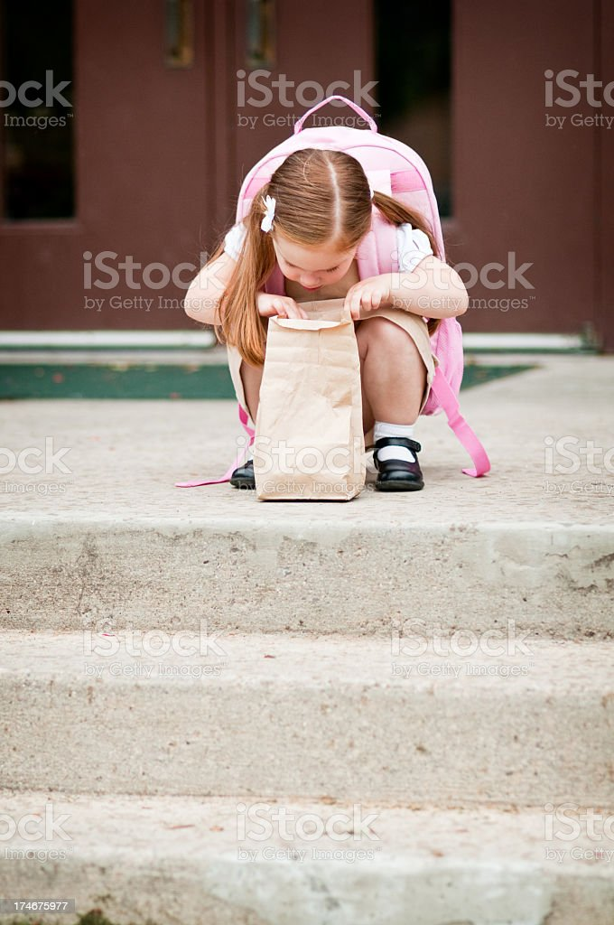 Preschool Girl Student Looking in Lunch Bag stock photo