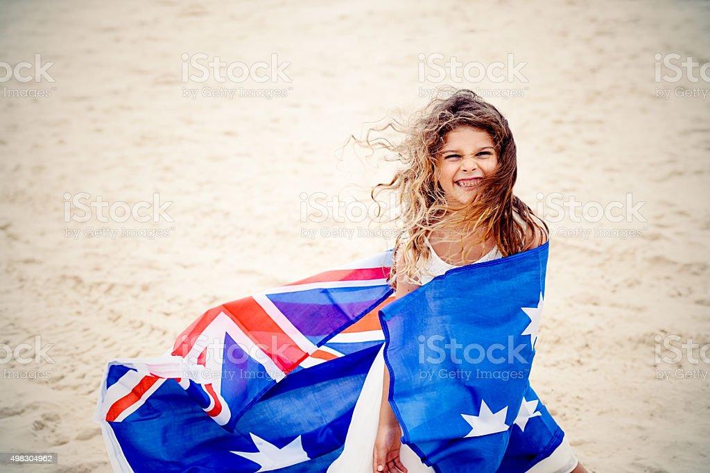 Preschool girl with Australian flag on the beach stock photo