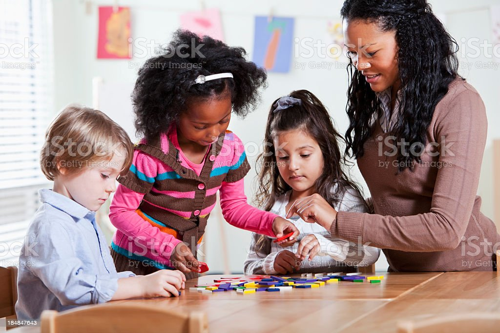 Preschool students with teacher in classroom stock photo