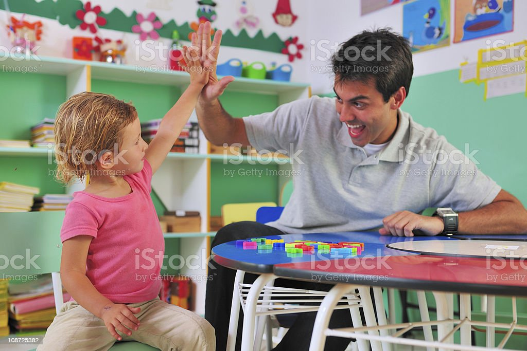 Preschool teacher and child giving a high-five stock photo