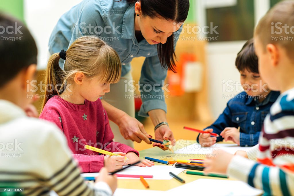 Preschool teacher and children drawing and coloring in their classroom stock photo