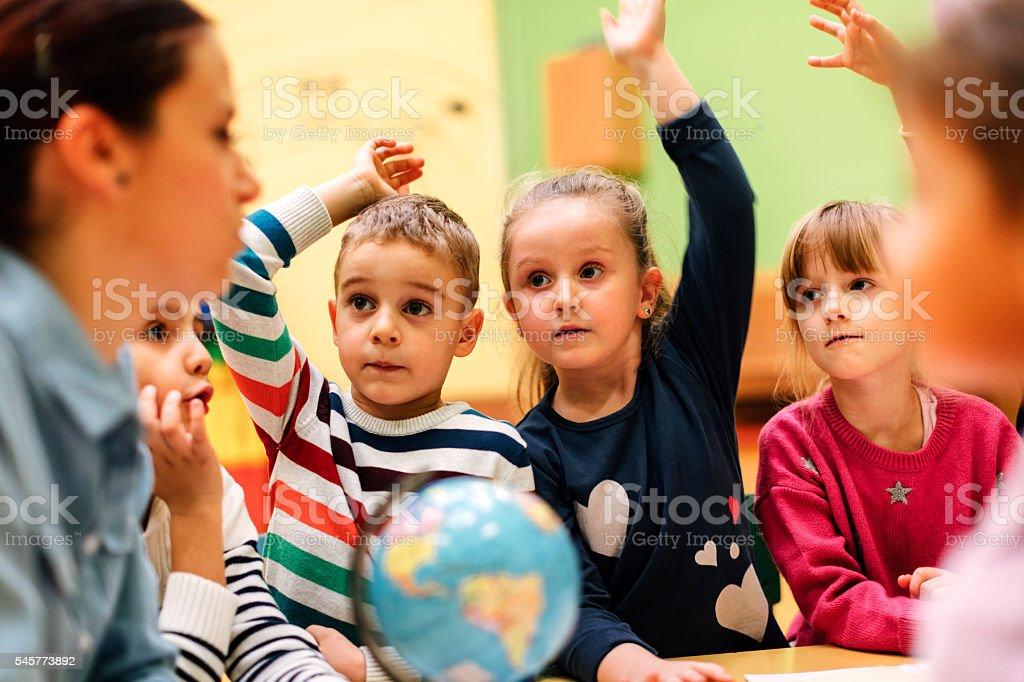 Preschool teacher and children in classroom stock photo