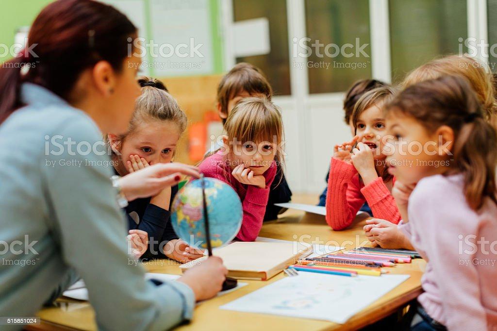 Preschool teacher and children using globe. stock photo