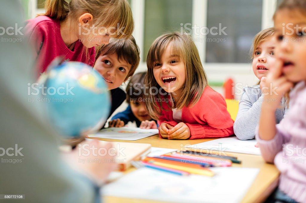Preschool teacher teaching her children about geography. Using globe...