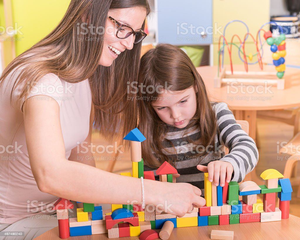 Preschool Teacher and Kid Building With Wooden Toy Blocks stock photo