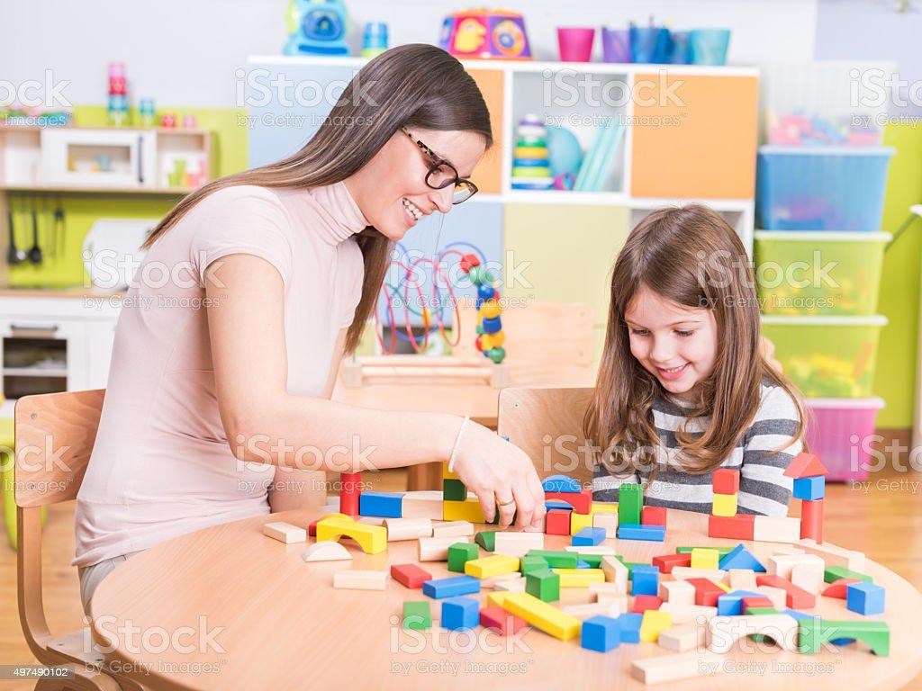Preschool - Kindergarten Teacher and Kid Playing with Wooden Building...