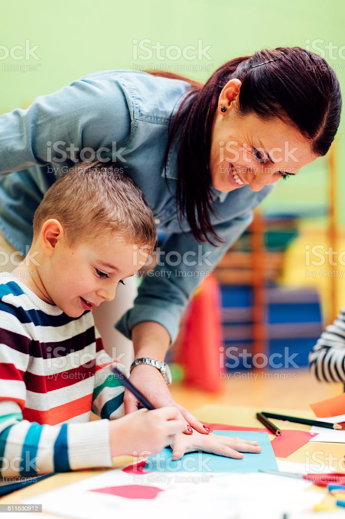 Preschool teacher assisting to cute boy in classroom stock photo